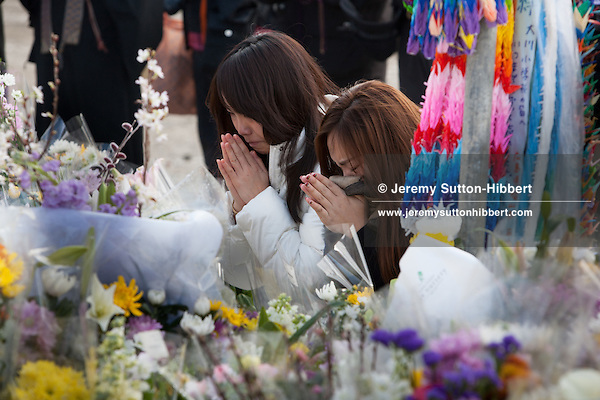 Teenage girls cry and pray at the shrine which stands beside Okawa Elementary School- a school in which 74 children and 10 teachers lost their life due to fatal indecision on the teacher's part on where to evacuate the children to after the earthquake hit but before the tsunami struck, on the 1 year anniversary of the March 11th 2011 earthquake and tsunami, in Kamaya, Tohoku region, Japan on Sunday 11th March 2012.
