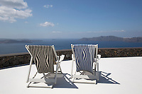 A pair of deck chairs with seats of reversible cotton in wavy stripes designed by Jean Paul Gaultier for Lelievre is placed to take full advantage of the spectacular view from the roof terrace