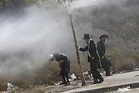 Ultra-Orthodox Jewish man take cover from police water jet in Ramat Beit Shemesh West of Jerusalem on August 12 2013, after Several dozen of Haredim protest against desecration of ancient graves were discovered at a new housing construction site. Some 14 Ultra-orthodox Jews were arrested. Photo by Oren Nahshon