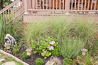 Pet Memorial Garden next to deck, with golden retriever statue, ornamental grasses, hydrangea, solar lights