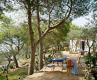 Garden tables and chairs are arranged in informal groups on this brick terrace surrounded by cacti, pine and olive trees