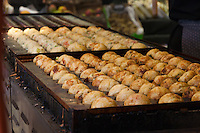 Takoyaki cooking on the grill during a demonstration of takoyaki cooking at Mitsuwa Market in Costa Mesa, California.  The batch in front is nearly done; the batch in back has just been formed into balls.