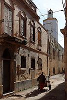 """Low angle view of a narrow street of the old city with a man pushing a cart, Portuguese Fortified city of Mazagan, El Jadida, Morocco, with the pentagonal minaret of the Grand Mosque in the background. El Jadida, previously known as Mazagan (Portuguese: Mazag""""o), was seized in 1502 by the Portuguese, and they controlled this city until 1769. Picture by Manuel Cohen"""