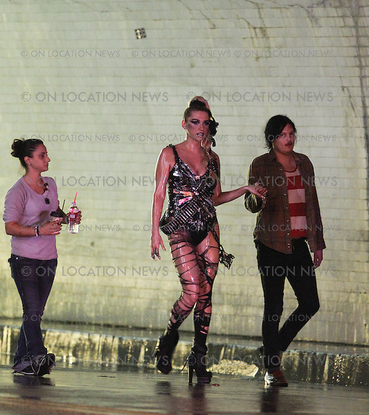 November 01st, 2010 Los Angeles, California. ***EXCLUSIVE*** Ke$ha films a music video for &quot;We R Who We R&quot;, a song she wrote in response to the recent gay youth suicides and bullying. Ke$ha was seen looking sexy and hard edged on the set of the Hype Williams directed music video. Ke$ha wore silver lipstick, sexy boots, a chain with locks, bullets, torn leggings and an outfit that looked like a broken mirror. She danced and performed all night long with &quot;her crew&quot; of diverse girls in a Downtown LA street tunnel which was rigged with fire and explosions to go off as the girls walked and danced through the Tunnel. There was also a car drag race scene filmed in the tunnel. Photo by Eric Ford/ On Location News. <br />
