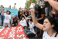 Phoenix, Arizona. April 25, 2012 - Sandra Castro (right), an organizer with the Puente Movement, chants as she sits in the middle of Central Avenue along others who blocked the street in protest of SB 1070. About 500 people protested the controversial law on the same day U.S. Supreme Court justices heard legal arguments on the Arizona vs. United States case. At the end of the march, six activists blocked Central Avenue by sitting in the middle of the street. They all were arrested by the Phoenix Police Department and taken to the Fourth Avenue County Jail. Photo by Eduardo Barraza © 2012