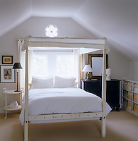 A simple bedroom in the eaves of this country house with a four-poster bed painted white