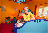 BNPS.co.uk (01202 558833)<br /> Pic: PhilYeomans/BNPS<br /> <br /> Artist Mary Rose Young in one of the bedroom's.<br /> <br /> Britain's wackiest property has come on the market...And the estate agents mantra of paint everything magnolia has definately not been applied.<br /> <br /> It may look like an idyllic cottage in the Forest of Dean from the outside but ceramic artist Mary Rose Young's unique taste has transformed the interior into what looks like something from Alice in Wonderland.<br /> <br /> The three-bedroomed house is decorated from head to toe in crazy colours, clashing patterns, and enormous murals,<br /> each room is covered in the garish designs, including the bathroom, where even the sink and toilet have been adorned in bright tiles.<br /> <br /> Estate agents Bidmead Cook now have the tricky task of showing prospective punters round the &pound;500,000 property.