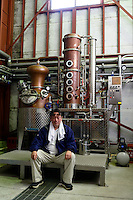 Munehiro Sata, President of Sata Souji Shoten Shochu Distillery, sitting by a brandy still. Minami Kyushu, Kagoshima Pref, Japan, December 21, 2016. The Sata Souji Shoten Shochu Distillery makes shochu spirits from local sweet potatoes. In recent years the distillery has imported grappa, brandy, calvados stills from Europe to experiment with new distilling techniques. They have attracted considerable attention from the media and other distillers as leading innovators in their industry.