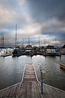 Berths, empty and occupied, under ominous, cloud-filled skies at the San Leandro Marina on San Francisco Bay.