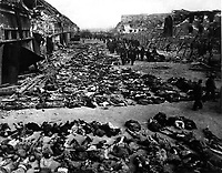 Rows of bodies of dead inmates fill the yard of Lager Nordhausen, a Gestapo concentration camp.  This photo shows less than half of the bodies of the several hundred inmates who died of starvation or were shot by Gestapo men.  Germany, April 12, 1945.  Myers.  (Army)<br /> NARA FILE #:  111-SC-203456<br /> WAR &amp; CONFLICT BOOK #:  1121