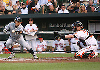 Ichiro Suzuki #51 of the Seattle Mariners bunts in front of Matt Weiters #32 of the Baltimore Orioles during a MLB game at Camden Yards, on August 8 2010, in Baltimore, Maryland. Orioles won 5-4 in extra innings.
