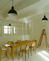 The dining area is separated from the living area by the original half glazed wall and lit by vintage enamelled pendant lights