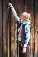 Caucasian woman measuring old wooden wall  using tape measure