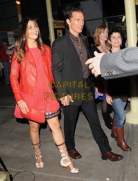 """CAMILA ALVES & MATTHEW McCONAUGHEY.at The Nobelity Project's inspiring new feature documentary """"One Peace At A Time"""" held at The Arclight Theatre in Hollywood, California, USA, .October 21st 2009..full length red leather jacket couple pregnant maternity top maternity holding hands brown shirt grey gray black suit   white lace up strappy sandals shoes open toe                                                             .CAP/RKE/DVS.©DVS/RockinExposures/Capital Pictures."""
