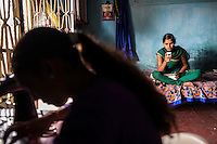 Video Volunteer videojournalist Niru J. Rathod (right), 24, looks through her video footage on her camera while her sister Kailash (left), 19, sews clothes for customers at home in Surendranagar, Gujarat, India on 14 December 2012. While Niru's sisters have become seamstresses or housewives, Niru, the 8th child in a family of 11 girls born to a Dalit construction worker, has been using videography for social change since 2006. She shoots and produces her own short documentaries and is a committed video activist, having conducted hundreds of village video screenings where she also speaks to thousands of men, shattering their ideas about what a woman and a Dalit can do while bringing massive changes to the communities she documents. Photo by Suzanne Lee / Marie Claire France