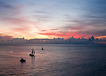 Tourist sailing cruises return to port at sundown.  Key West, Florida, USA.