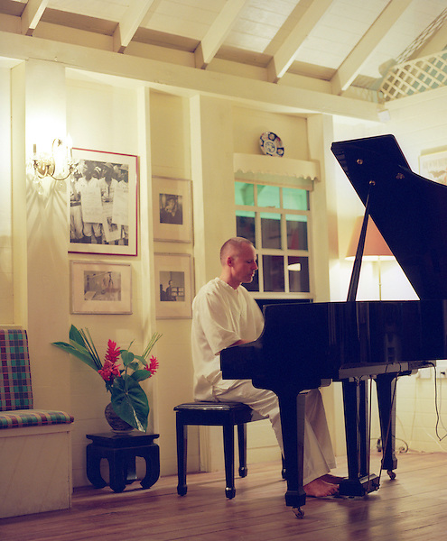 CASTLE BRUCE, DOMINICA : Beau Rive owner and British ex-pat Mark Steele plays the piano for guests in the roof top terrace bar at Beau Rive Hotel in Dominica. Beau Rive is situated 240 feet above sea level on the East (Atlantic) coast between the villages of Castle Bruce and Sineku. The hotel is nestled into a hillside amid three acres of tropical gardens and forest, with a dramatic view of the ever-crashing waves at Anse Francais and Wakaman Point. Dominica.