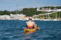 A kayaker enters the busy harbor and marina of Mackinac Island Michigan on Lake Huron.