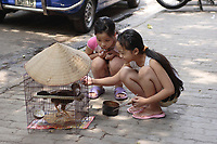 Hanoi<br /> , Vietnam - 2007 File Photo -<br /> <br /> <br /> Two young Vietnamese girls feed a chicken in a cage.<br /> <br /> <br /> photo : James Wong-  Images Distribution