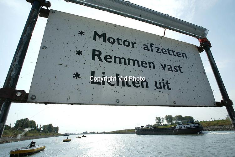 Foto: VidiPhoto..TOLKAMER - De Rijn heeft maandag bij Tolkamer een nieuw laagterecord bereikt tussen de 7.05 en 7.07 meter beneden NAP. Het vorige record stond op 7.13 meter. De lage waterstand trekt de nodige belangstelling, terwijl het scheepvaartverkeer steeds meer last krijgt om goed te manoevreren. Foto: Bij Pannerden wordt de Rijn wel erg smal.