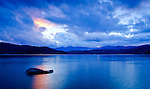 Idaho, North, Coeur d'Alene. A hole in the autumn sky illuminates a rock and the water of Lake Coeur d'Alene with pink color.