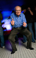 A retired senior dances on the dance floor at a nightclub for fun and exercise.  He goes dancing at local exciting hot spots several times a week to stay fit.