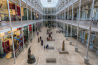 Central Hall at the National Museum of Scotland, Edinburgh.  .The National Museum results from a merger of the Museum of Scotland, built in 1998, and the former Roayal Museum, built in 1861. After a massive renovation, the building re-opened in July 2011.  Going through the different halls, and passing from the new to the old from one hall to the next is a peculiar yet pleasant characteristic of the museum.  .Pictured is the great hall, part of the former Royal Museum, with its cast iron contrusction rising the full height of the building, and ending in a magnificent skylight.