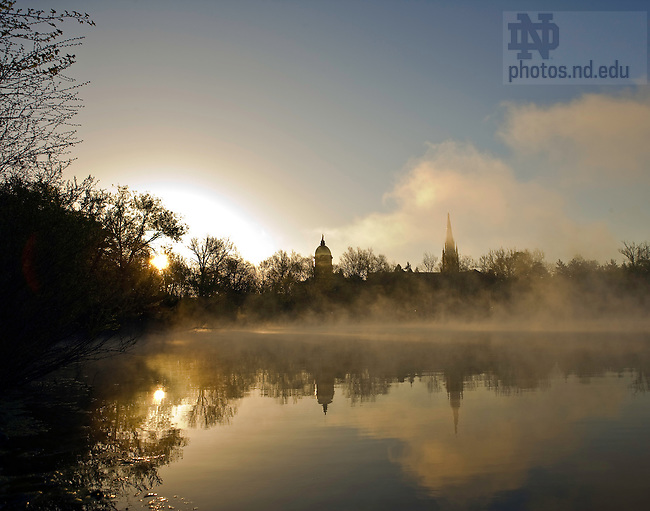 St. Joseph Lake in the early morning with the Basilica of the Sacred Heart and the Main Building..Photo by Matt Cashore..