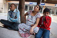 Leela Mekwan (center), 34, sits with her husband Jayantibhai (left), 38, and son Ashish (right), 14, in the Akanksha IVF and surrogacy center in Anand, Gujarat, India on 9th December 2012. Leela is 9 months pregnant with her 2nd surrogacy that she is doing with Dr. Nayana Patel and has support from her immediate family including her 2 sons. Photo by Suzanne Lee/Marie-Claire France