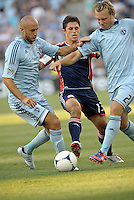 Ryan Guy (13) midfield New England Revolution stopped by Sporting KC defenders Aurelien Collin (78)  and Michael Harrington (2).Sporting Kansas City and New England Revolution played to a 0-0 tie at LIVESTRONG Sporting Park, Kansas City, KS.