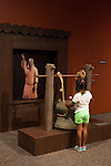 "A young girl bangs a gong at the ""Terra Cotta Warriors: The Emperor's Painted Army,"" Exhibit directly from Xian in the Shaanxi Province, China which debuted in 2014 at the Children's Museum, Indianapolis, Indiana, USA"
