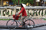 A woman rides a bicycle near the Citadel in Hue, Vietnam. April 22, 2013.