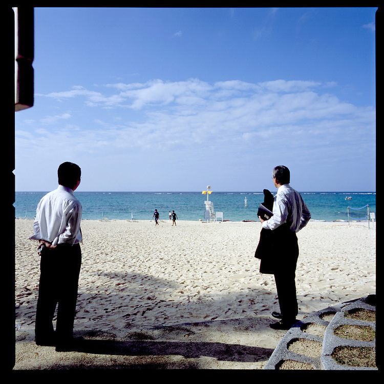 "Japanese ""salarimen"" wait for their boss to come off of the beach at Moon Beach Hotel, Okinawa, Japan."