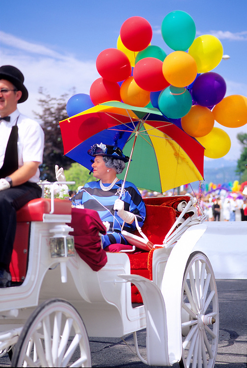 Parade Queen in elegant, white horse-drawn carriage, with balloons and umbrella at Gay Pride Parade, in the West End of Vancouver, BC.