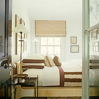 A guest bedroom is furnished with a French vintage parchment-covered bed