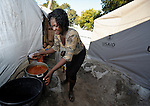 A woman cooks in front of her tent home in the Petionville Camp at the edge of Port au Prince, Haiti. With some 50,000 residents packed onto what was once a golf course, it's the largest camp of hundreds of locales hosting more than a million people left homeless by the January 12, 2010 quake.