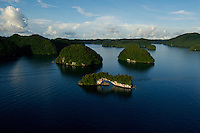 Aerial view of the Rock Islands in the late afternoon with the Natural Arch in foreground Palau, <br /> Micronesia