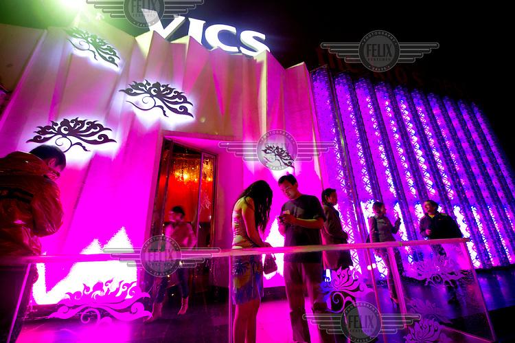 The exterior of Vics Nightclub illuminated with purple light.