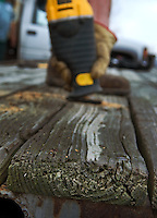 A reciprocating saw cuts through a plank on a dock. Workers repair boat and fishing docks for Hoover Reservoir in Columbus, Ohio.  Some of the board replaced were more than 30 years old.