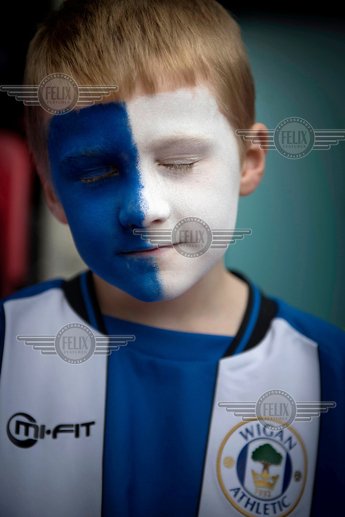 A young Wigan Football Club fan with a replica shirt and his face painted in the team's colours. /Felix Features