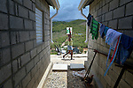 """A woman carries water past houses in a model resettlement village constructed by the Lutheran World Federation in Gressier, Haiti. The settlement houses 150 families who were left homeless by the 2010 earthquake, and represents an intentional effort to """"build back better,"""" creating a sustainable and democratic community."""