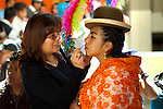 Young Bolivian cholita dressed in bowler hat and manta or shawl, the traditional indigenous Aymaran costume, gets help with her makeup on Independence Day in La Paz, Bolivia.