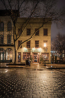 Stone and brick architecture along Saint Anthony Main street in Minneapolis, Minnesota at night after rain shower.
