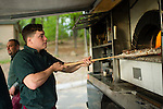WATERTOWN, CT- 19 May 2016-051916EC12-  Chris Catania, with the Big Green Pizza Truck out of New Haven, checks on a pizza during the Greater Waterbury Campership Fund's annual fundraiser Thursday night. The event was held at the Greater Waterbury YMCA's Camp Mataucha in Watertown. All money raised goes directly to the cost of sending children to camp. Erin Covey Republican-American