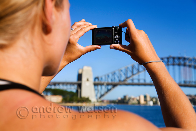 A woman photographs the Sydney Harbour Bridge.  Sydney backpacker.  Sydney, New South Wales, AUSTRALIA