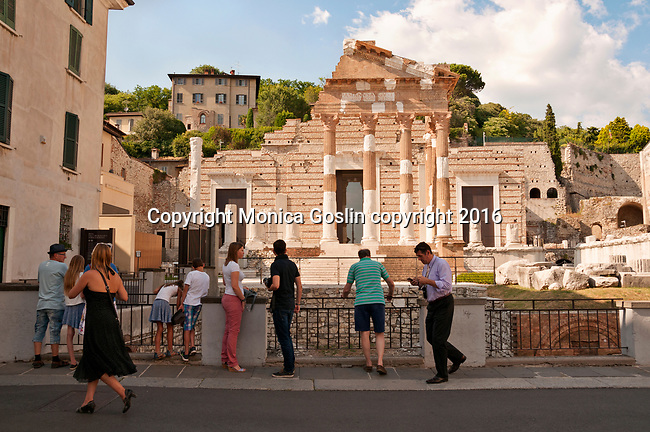 Tourists look and take pictures of the Capitolium, or Capitoline Temple, which is part of the Roman Museum in Brescia, Italy