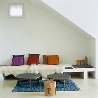 A contemporary banquette beneath a flight of stairs is accessorised with coloured cushions and sheepskin rugs