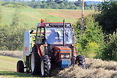 Farm tractor bailing hay with round baler