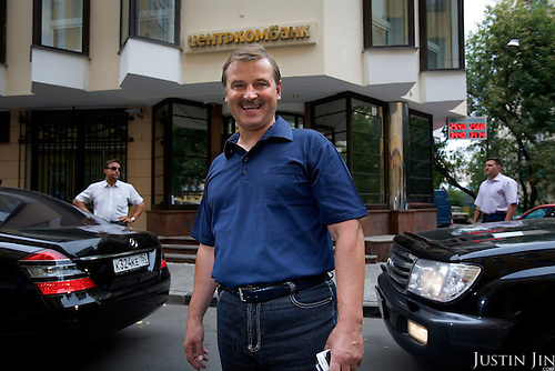 Russian billionaire Sergei Veremeenko poses in front of his bank in Moscow, Russia, near his armed bodyguards and his cars.