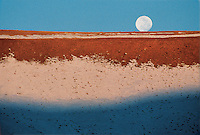 The moon rises over a hillside in the United States.
